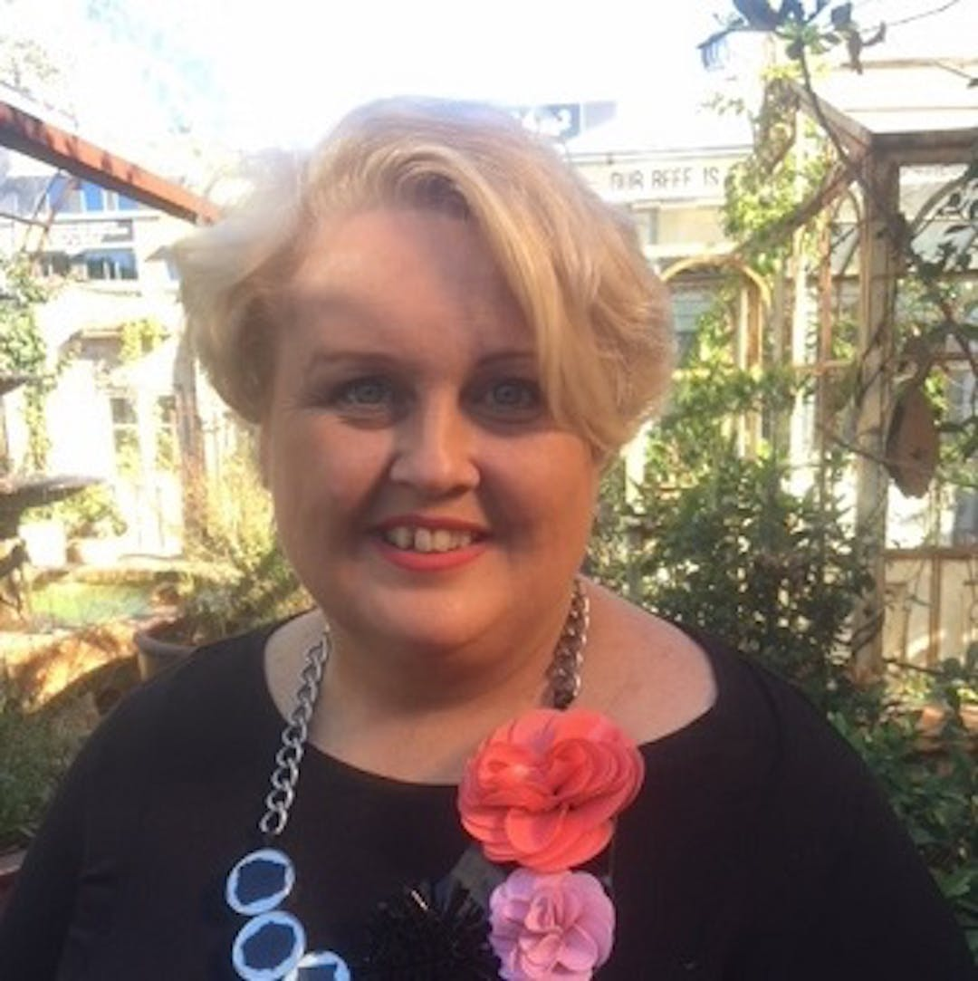 Woman with short curly blond hair smiling broadly at the camera, wearing a black shirt and colourful chunky necklace, standing in a garden.