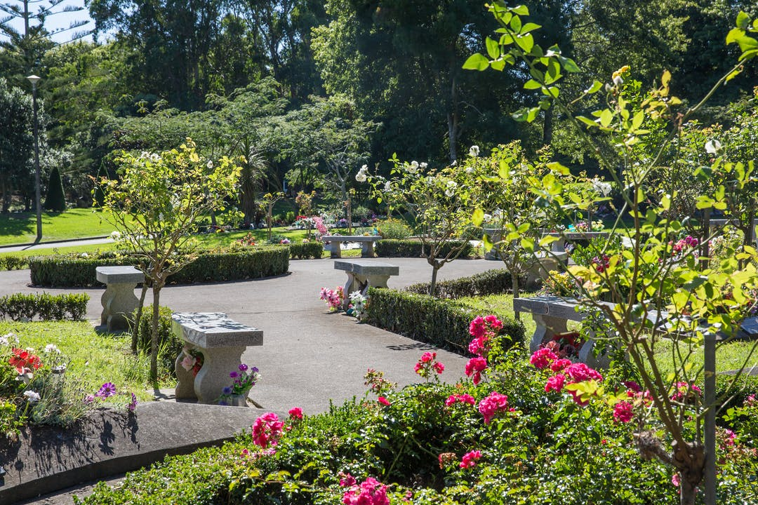 Image of a seating area in a cemetary with benches for sitting on and a garden with flowers around them.