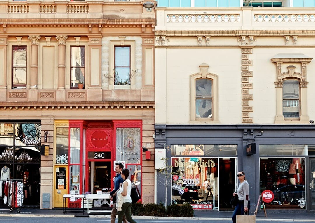 3 People shopping in Rundle Street. In the background you can see beautiful historic buildings that have converted to shops.