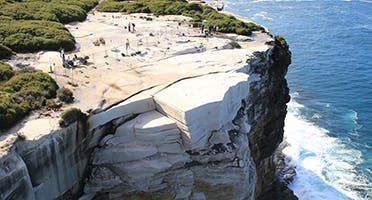 This image taken by a drone shows how Wedding Cake Rock is sitting precariously on unstable rock high above the ocean and how it is almost completely separated from the land by a large crevice. Photo: OEH