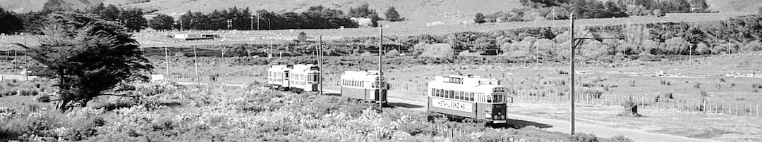 Historic photo of trams running along rail tracks within Queen Elizabeth Park, with tussock and farmland in the background