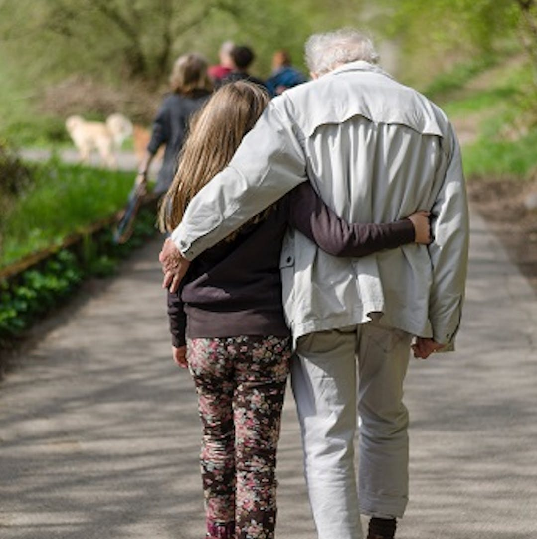 An elderly man and a young girl are walking away with their arms around each other. They are walking up a path through a sunny park. They look deep in conversation.
