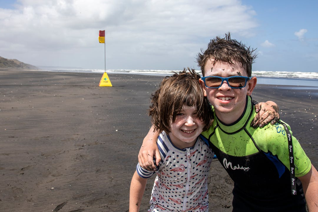 Children on a beach with a swimming flag in the background
