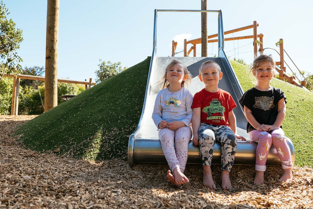 Children sat on a slide in playground