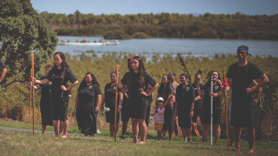 Māori community stood on the grass at the Pahurehure Inlet.