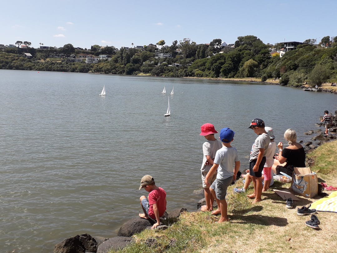 Adults and children gathered at the waterside