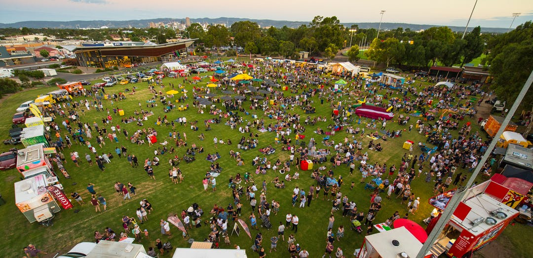 A birds-eye view of Kings Reserve during Summer Festival Fork in the Road. It is sunset and a large ring of food trucks surrounds a huge crows of people enjoying the festivities while the Adelaide Hills are far in the distance.
