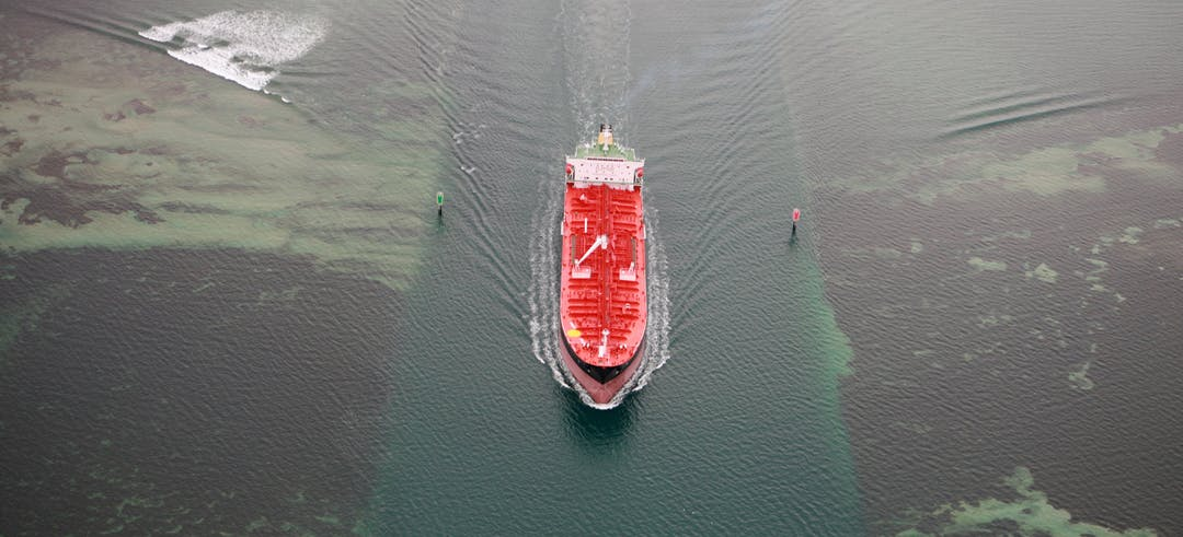 Red container ship in a shipping channel, with a red and a green marker pile on either side, showing a deep water channel and small bow waves