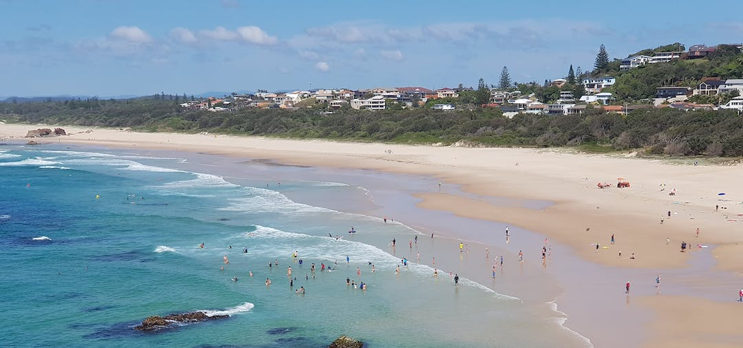 Panoramic view of Light House Beach in Port Macquarie, New South Wales, Australia showing sand and clear blue water with beach goers