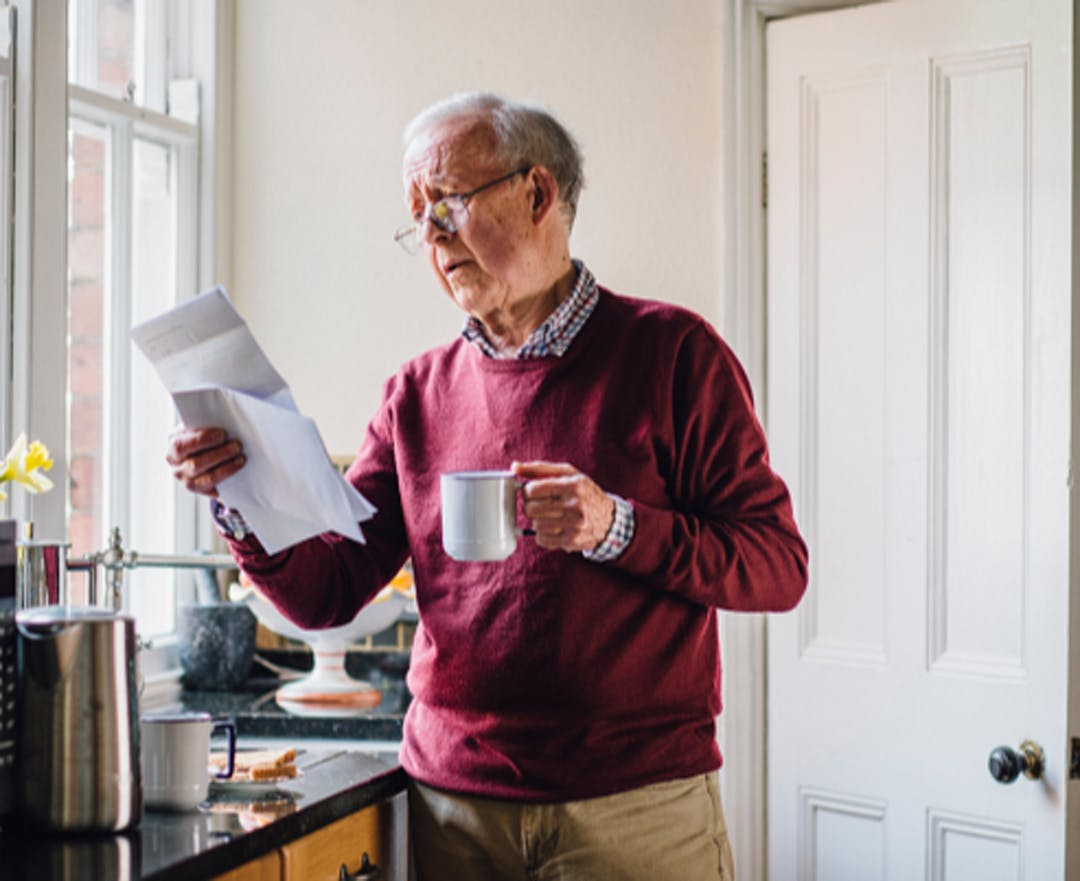 Older man in dark red jumper, looking worried while holding and reading papers. He is standing in a kitchen with a cup in his other hand.