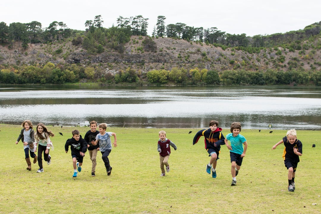 Children running on the grass with Valley Lakes in the background