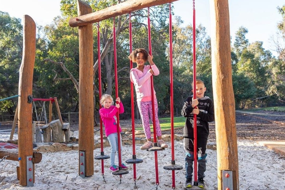 Children playing at local playground, smiling as they climb on the equipment.