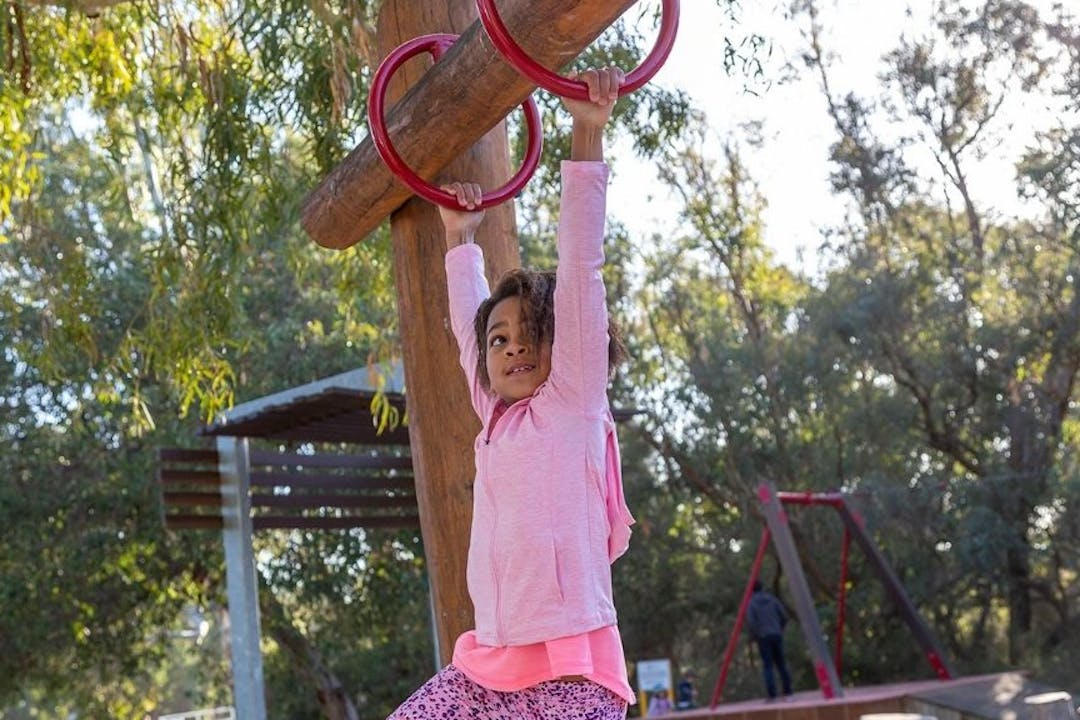 A child on the monkey bars at a playground