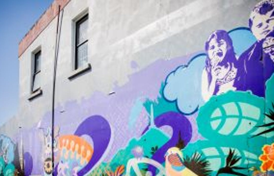 Onehunga laneway street art depicts two children eating ice-cream, plants, flowers and birds.