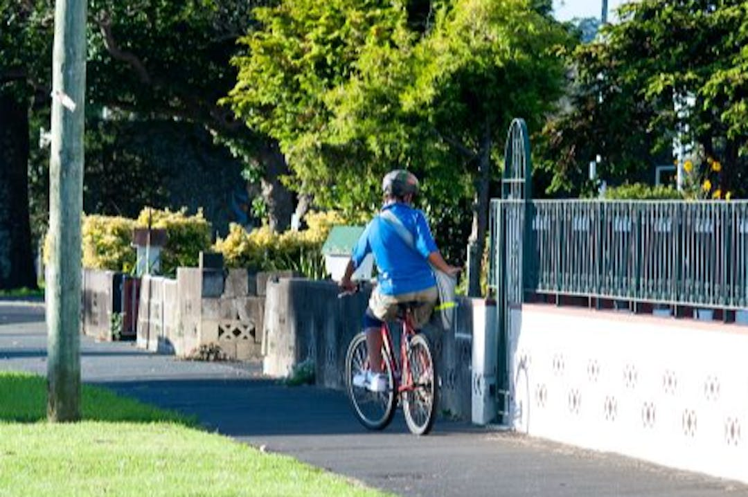 A young boy on a bicycle delivers newspapers in a Glen Innes neighbourhood.