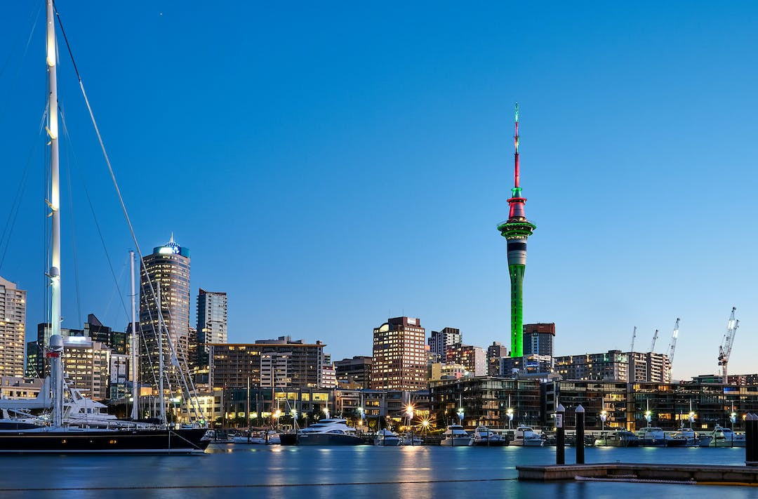 View of Auckland's Viaduct Harbour from the waterfront showing the Sky Tower and sailboats.