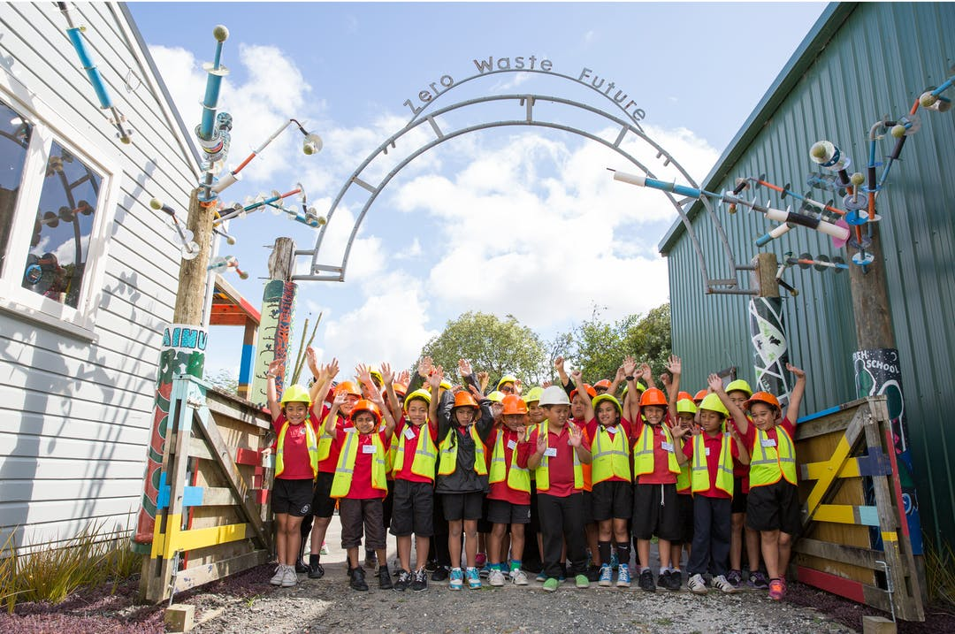 """A group of children in safety gear standing with their arms raised under an archway made of recycled material that reads """"Zero Waste Future"""""""