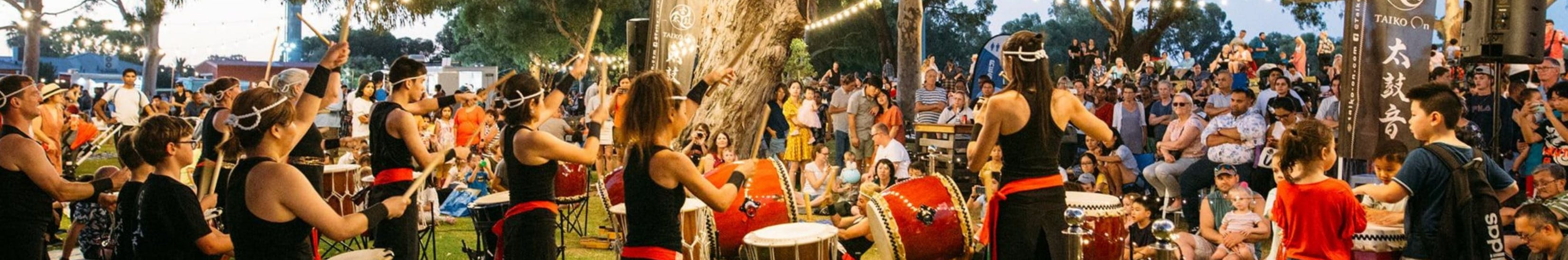 People of many backgrounds playing the drums at a festival