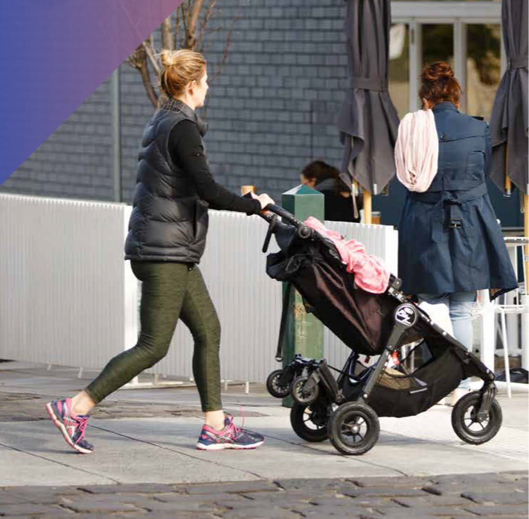 A woman walking on the footpath, pushing a pram past another woman waiting outside a cafe.
