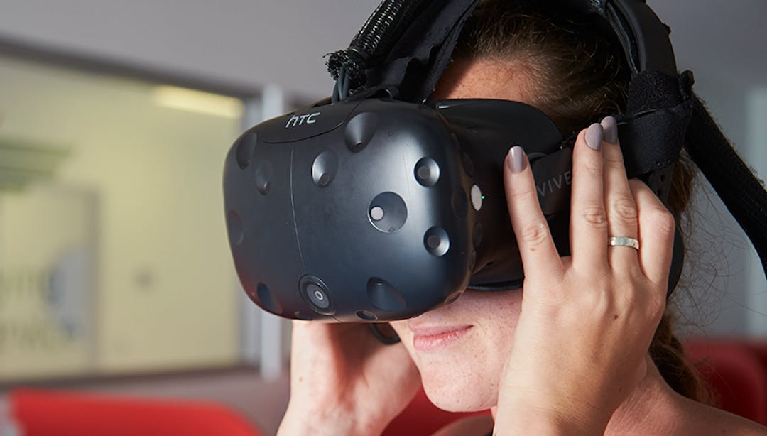 Image of a Territory woman using a HTC Virtual Headset to engage in a virtual / digital experience.
