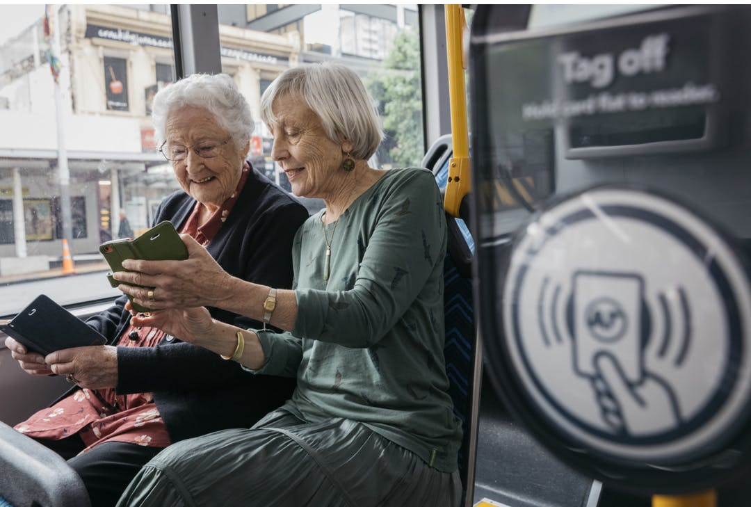 Older Citizens Using mobile phones on a Bus
