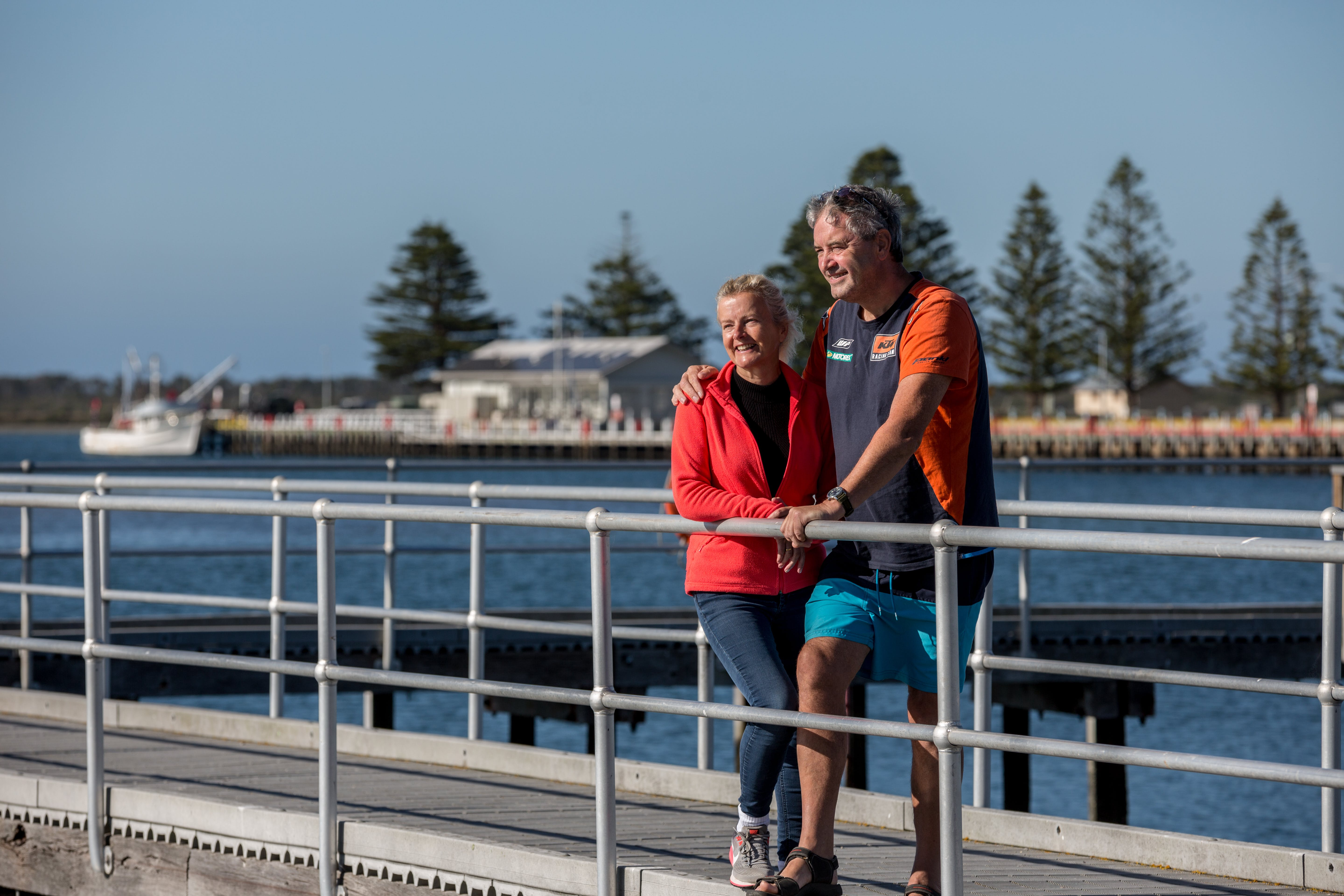 Man and Woman standing on pier at Port Albert overlooking the water.