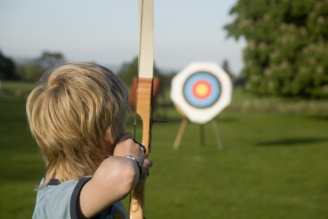 A child shooting an arrow at an archery target.