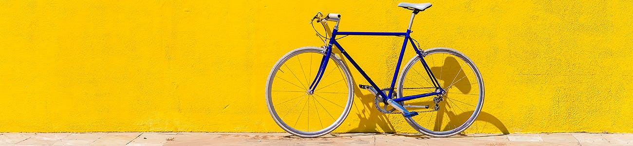 A bike in front of a yellow wall