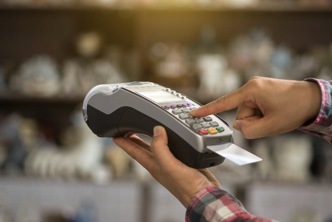 A person using a portable EFTPOS machine