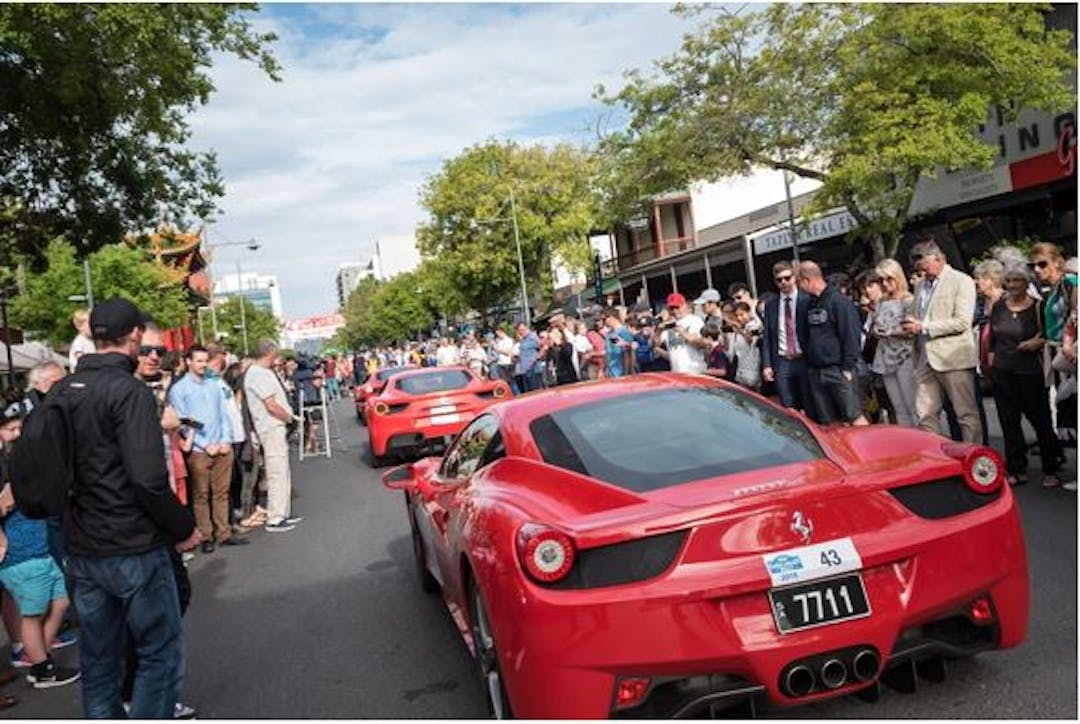 View of a crowded Gouger Street with people admiring the red rally cars that are parked up for display.
