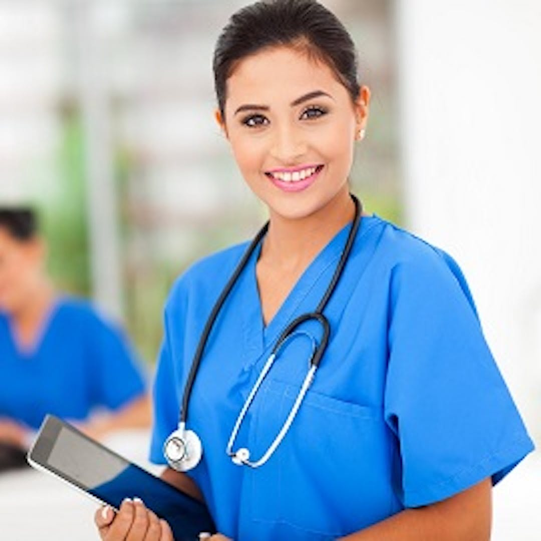 An young female health care worker smiles brightly at the camera. She is wearing bright blue scrubs and has a stethoscope hanging draped her neck and a tablet device in her hands.