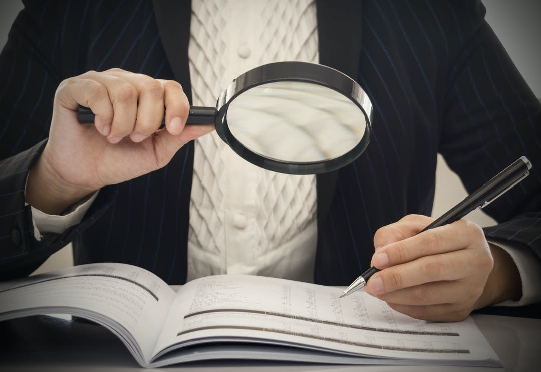 Stock image of person examining document with magnifying glass