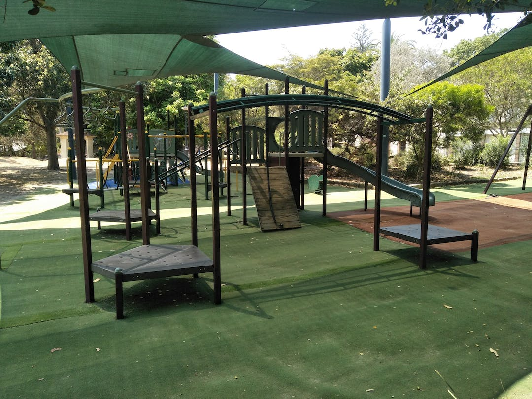 The image shows the playground equipment at Plumb Reserve on Fletcher street in Woollahra. It has a slide, climbing frame, shade sails and soft fall floor covering.
