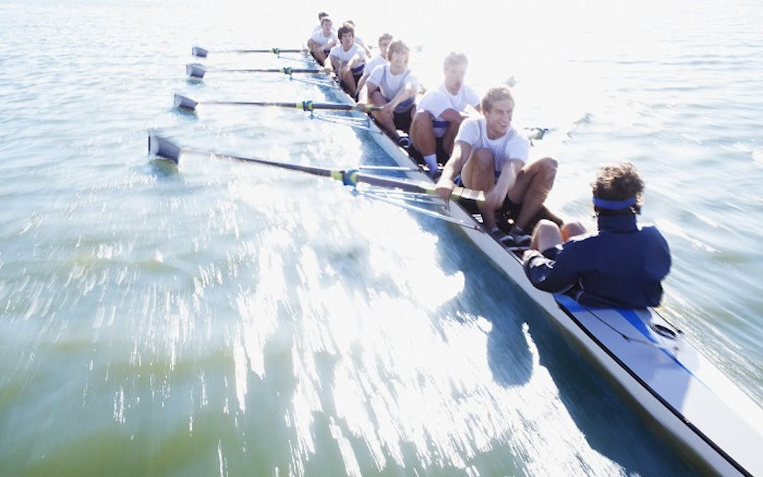 An eight- man rowing team rowing on a river