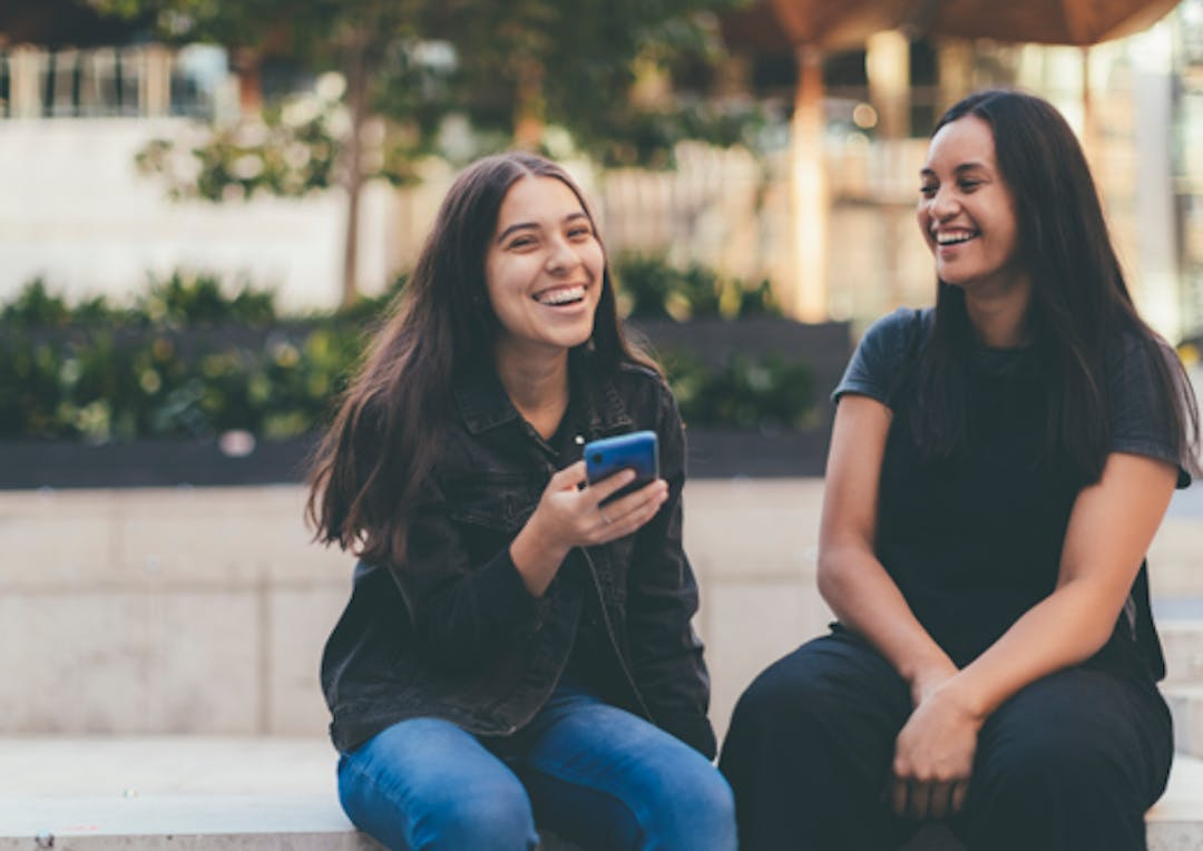 women smiling looking at i-phone