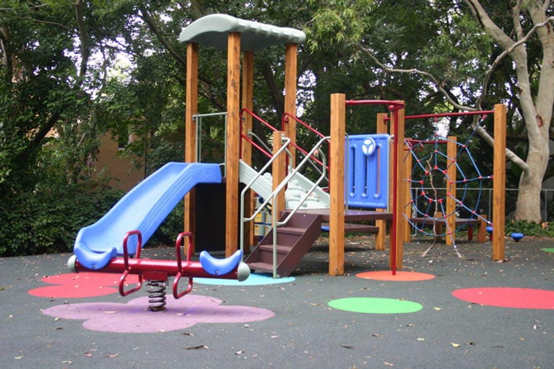 Image of the existing play equipment at Dillon Street Reserve, Paddington. It includes a slide off a raised decks with steps and a spring toy in the foreground. In the background there are trees and vegetation.