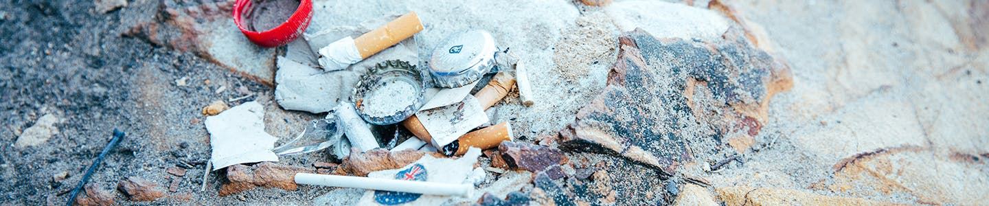 Cigarette butts, beer bottle lids and other rubbish on the ground