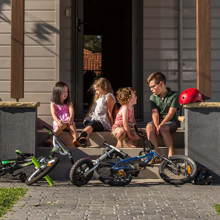 four children talking on front veranda, three bicyles at the front.