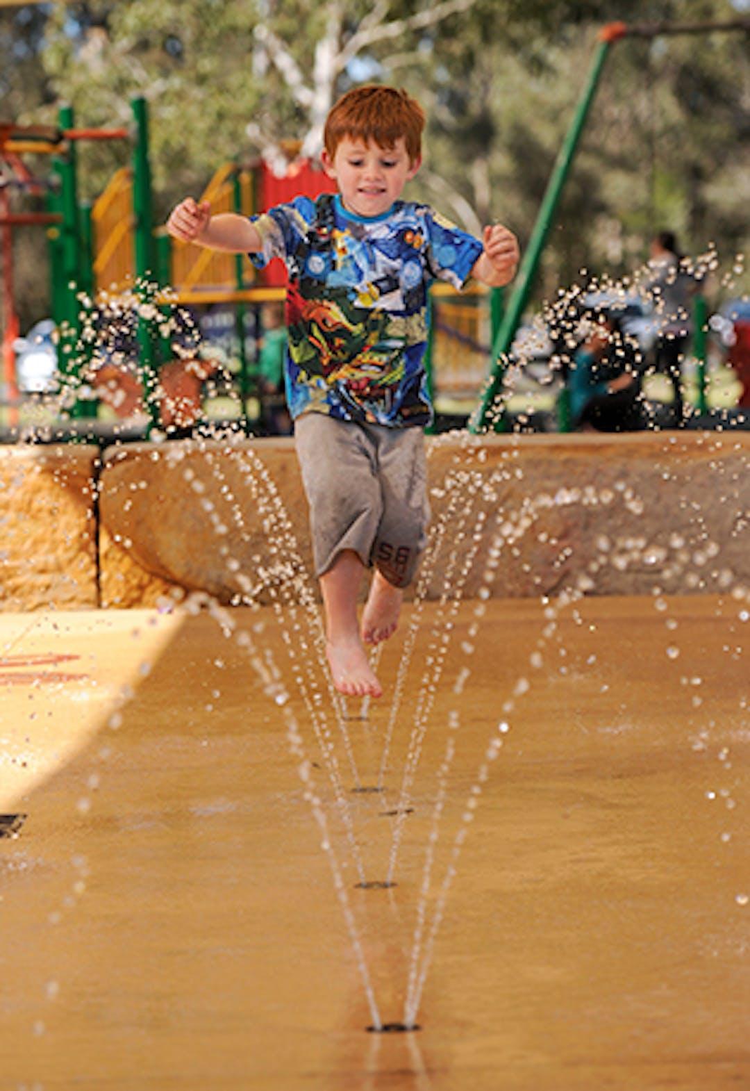 Young boy running through a water fountain