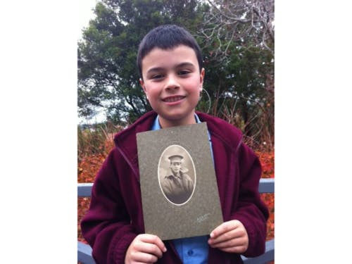 Proud Northbridge boy with photograph of his great-grandfather who served in WWI