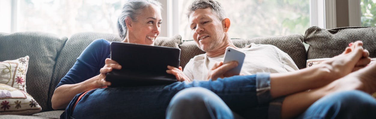 Image of woman and man on couch looking at mobile devices