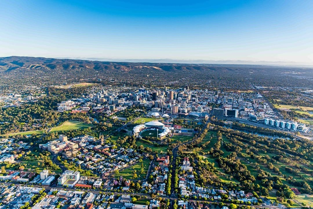 Ariel view of the City of Adelaide with the Adelaide Hills in the background framed by clear blue sky.