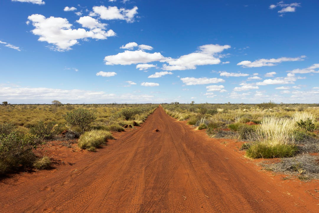 Photograph of unsealed section of the Gunbarrel Highway, Western Australia, surrounded by spinifex grass
