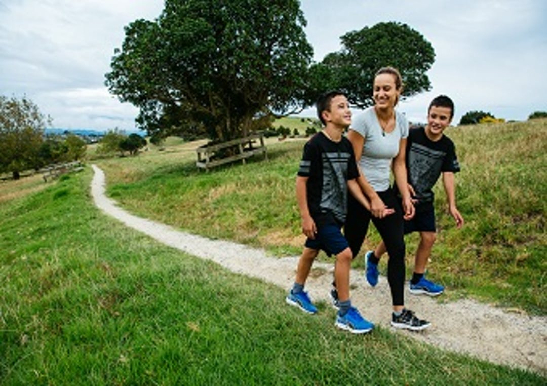 A mother and two sons stroll along a white stoned walk path running through Totara Park. Surrounding the path is green grass with some trees in the background.