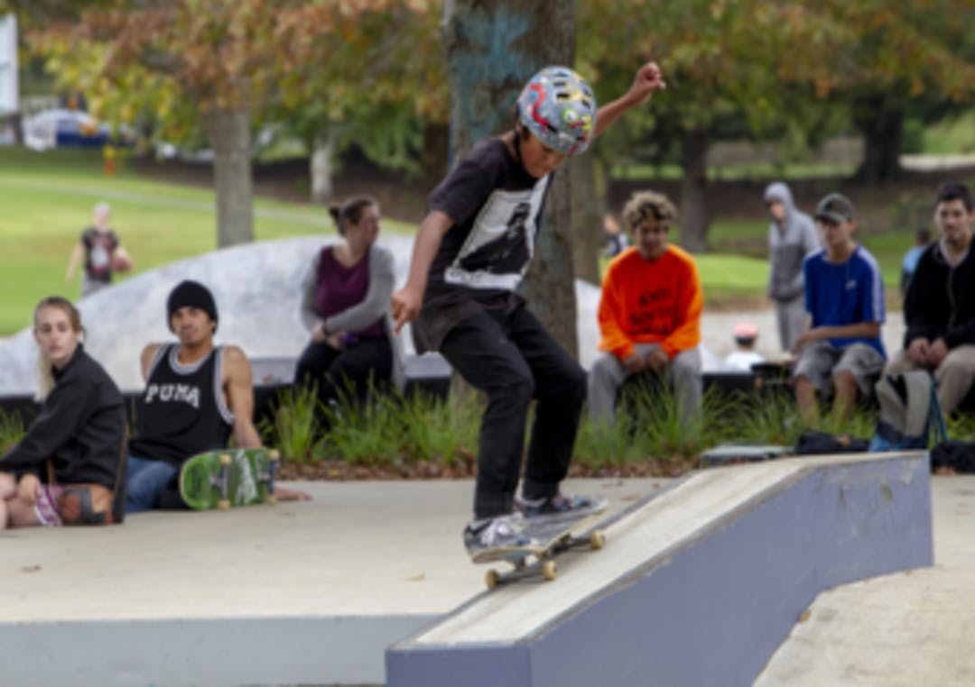 Ray Small Skate Park opening. A young boy skateboards  while a crowd looks on.