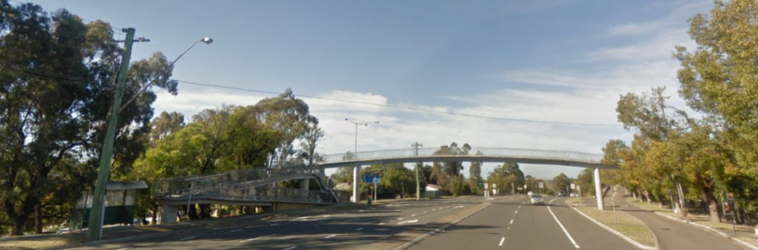Street view of the Pedestrian Bridge over the Great Western Highway at Valley Heights. The bridge has an accessible ramp on the left hand side and a long single span over the whole highway that has a gentle arc. The day is sunny and there are high clouds in the sky.