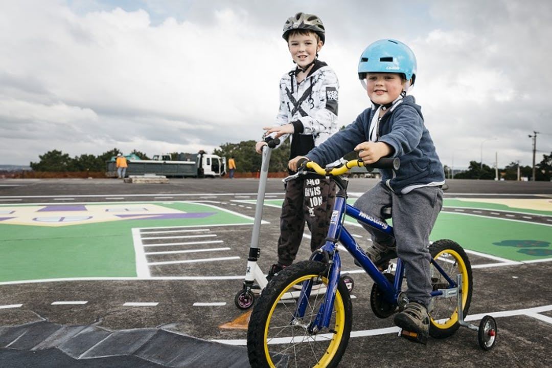 Two young boys ride a bike and a scooter on a painted court at Forrest Hill Reserve