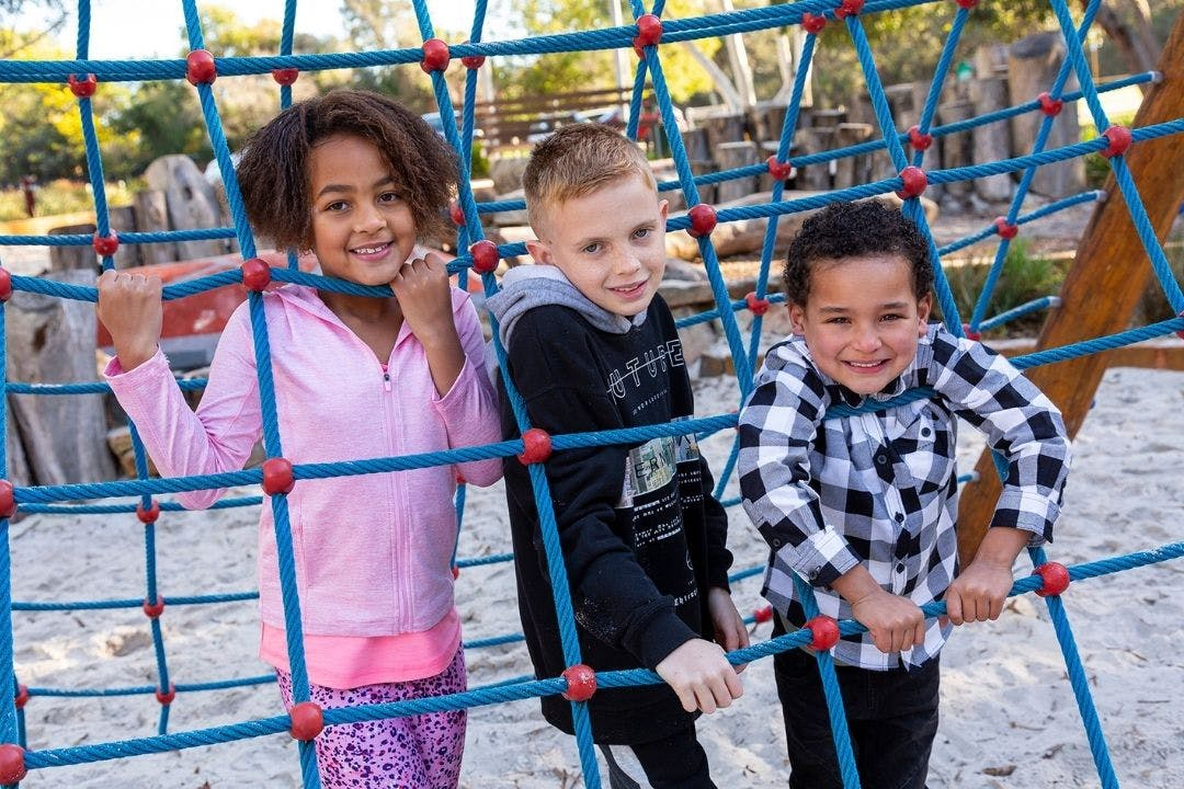Children playing at local playground, smiling as they climb on climbing net.