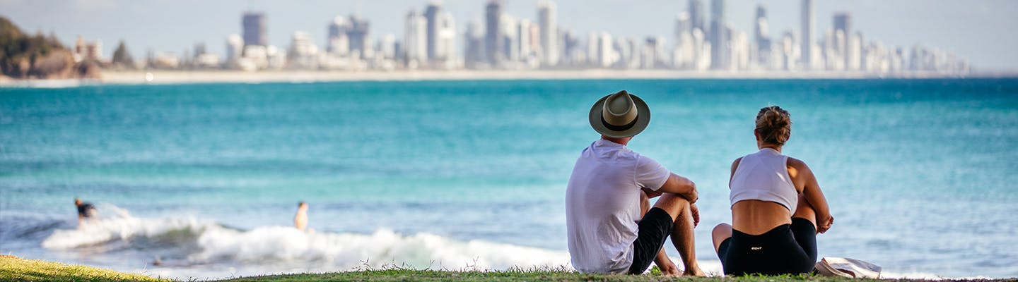 A young couple sitting on the Burleigh Headslands looking over the ocean towards Surfers Paradise