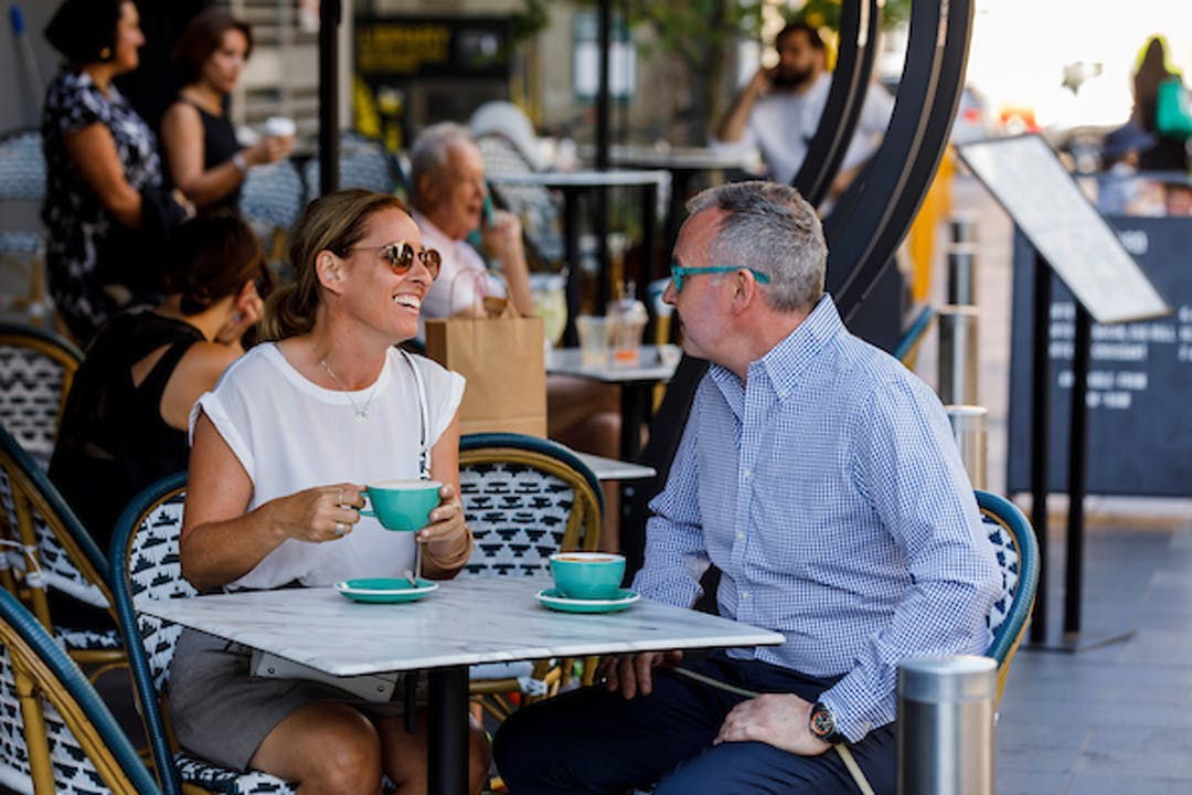 Man and woman sitting at outdoor table at a café in Kiaora Pl, Double Bay